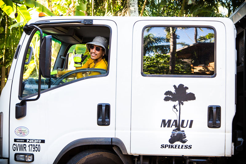 White colored Maui Spikeless dump truck with a happy smiling driver from Maui Spikeless.